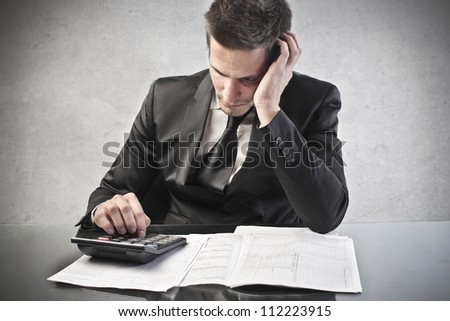 Businessman with a calculator. Concentration - stock photo