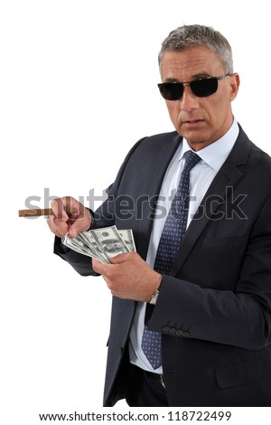 Businessman with a cigar and a fistful of dollars - stock photo
