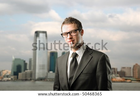 Businessman with a cigarette in his mouth with cityscape on the background - stock photo