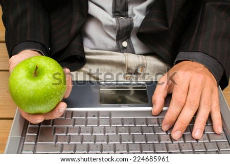 Businessman with a computer and an apple in his hand - stock photo