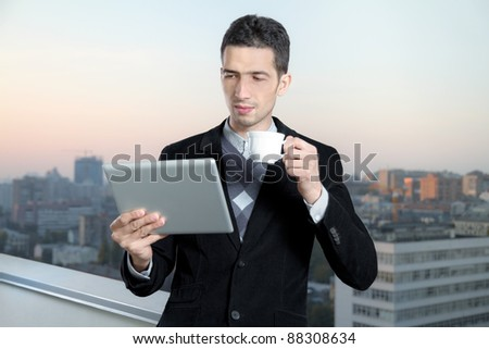 Businessman with a cup of coffee uses a digital tablet on the roof of business center. Cityscape on background. - stock photo