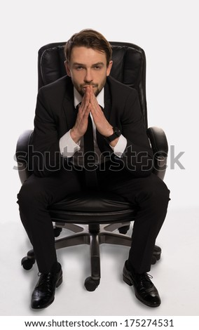 Businessman with a dilemma sitting in his office chair facing the camera with his hands steepled and a seerious contemplative expression as he tires to solve a problem or reach a decision, on white - stock photo