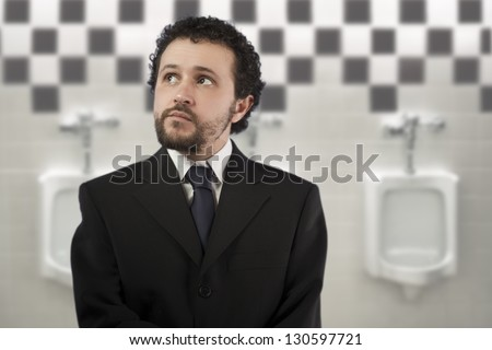 businessman with a distracted look urinating in urinals - stock photo