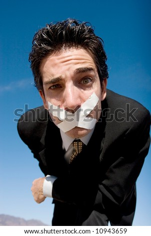 Businessman with a duct tape on his mouth - stock photo