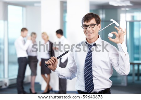 Businessman with a golf club against the staff office - stock photo