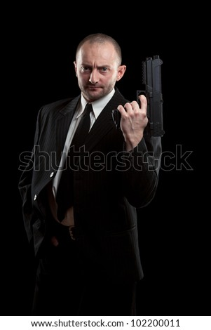 Businessman with a gun, isolated on black