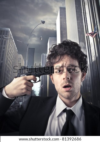 Businessman with a gun pointed at his temple - stock photo