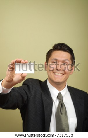 Businessman with a huge smile showing off his card; selective focus on the card - stock photo