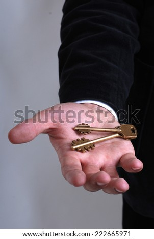 Businessman with a key in his hand - stock photo