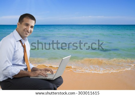 Businessman with a laptop at the beach - stock photo