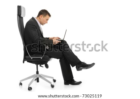Businessman with a laptop sitting in a chair in a bright office. Isolated on white background - stock photo