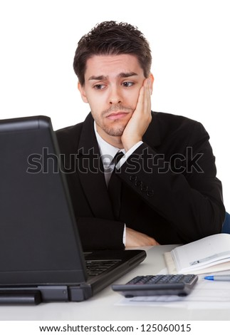 Businessman with a look of hopelessness staring at the screen of his laptop with his head resting in his hands - stock photo