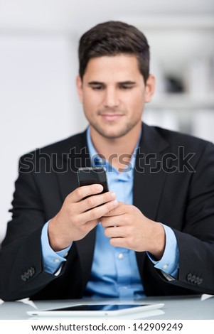 Businessman with a mobile phone sitting reading a message on the screen with a serious expression - stock photo