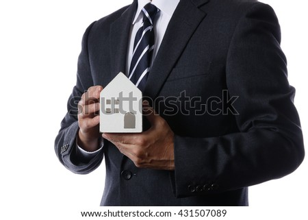 Businessman with a model of a House - stock photo