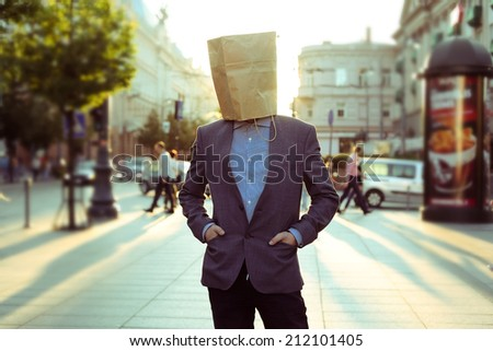 Businessman with a paper bag in the street - stock photo