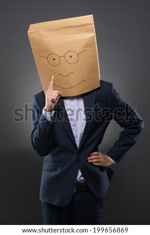 Businessman with a paper bag on his head pointing up with his finger - stock photo