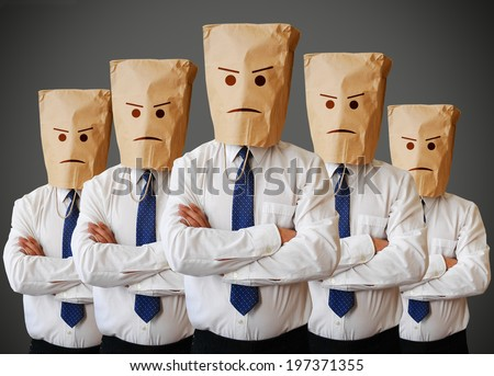 Businessman with a paper bag with angry face on it - stock photo