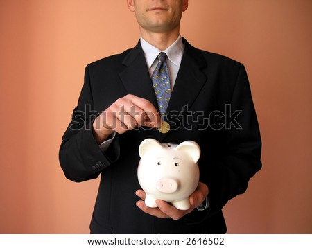Businessman with a piggy bank.He puts coin in a piggy bank. - stock photo