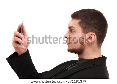 Businessman with a raised eyebrow using his phone screen isolated on white - stock photo