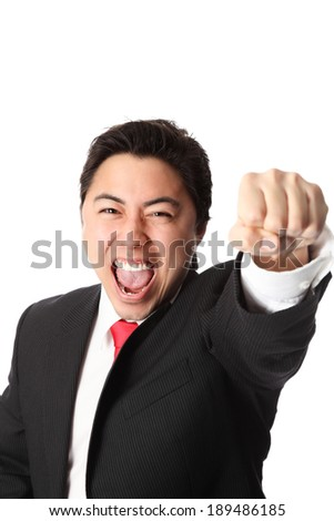 Businessman with a raised fist, wearing a suit and tie. White background. - stock photo