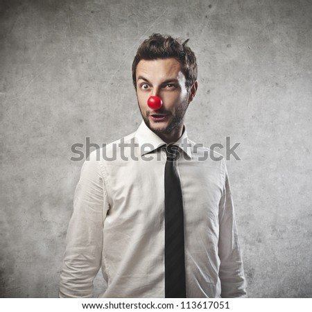 Businessman with a red clown nose - stock photo