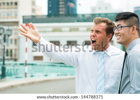 Businessman with a what-the-heck look on his face observing the downtown together with his colleague - stock photo