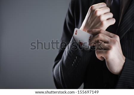 Businessman with ace card hidden under sleeve. - stock photo