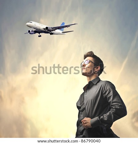 Businessman with airplane in the background - stock photo