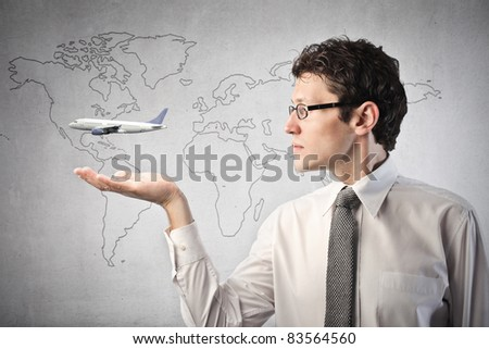 Businessman with airplane over his hand and world map in the background - stock photo