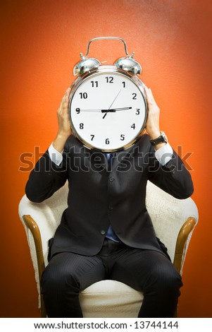 Businessman with alarm clock on head, studio shot.
