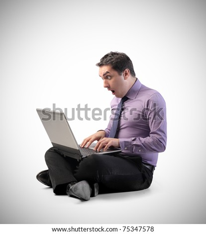 Businessman with amazed expression using a laptop - stock photo