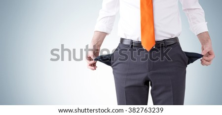 businessman with an orange tie turning his empty pockets inside out. Front view, no head. Grey background. Concept of bankruptcy.