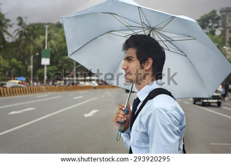 Businessman with an umbrella crossing a road - stock photo