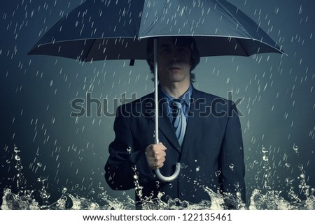 Businessman with an umbrella in the rain. - stock photo