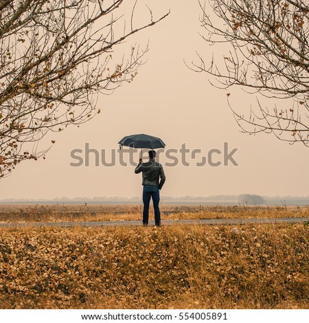 Businessman with an umbrella outdoors on field background