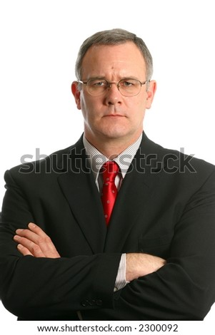 Businessman with arms crossed and serious expression - stock photo
