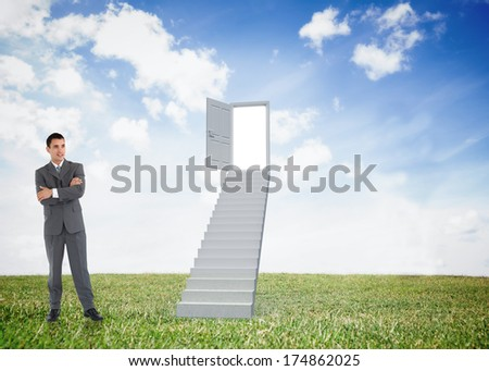 Businessman with arms folded against open door at top of stairs in a field
