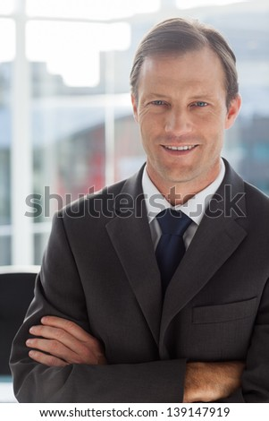 Businessman with arms folded in an office - stock photo