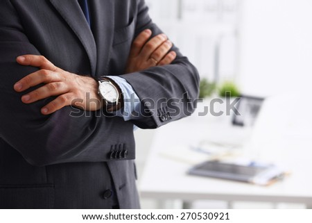 Businessman with arms folded standing in office - stock photo