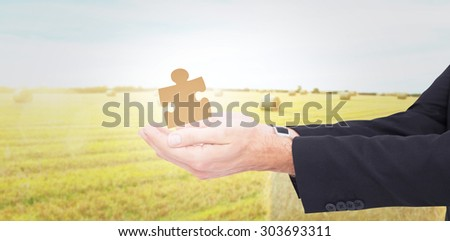Businessman with arms out presenting something against golden fields with hay bales - stock photo