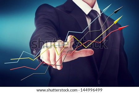 Businessman with arrows representing growth on a navy blue background - stock photo