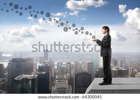 Businessman with at signs flying from his hands on the rooftop of a skyscraper - stock photo