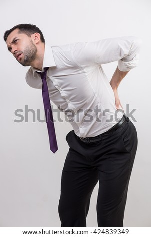 Businessman with back pain holds his back in a studio - stock photo