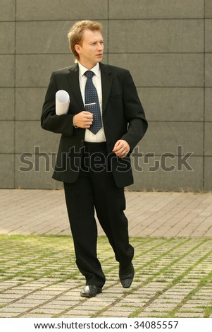businessman with bag and blueprint walking on the street