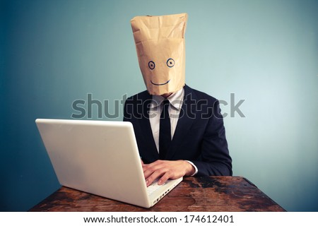Businessman with bag over head working on computer - stock photo