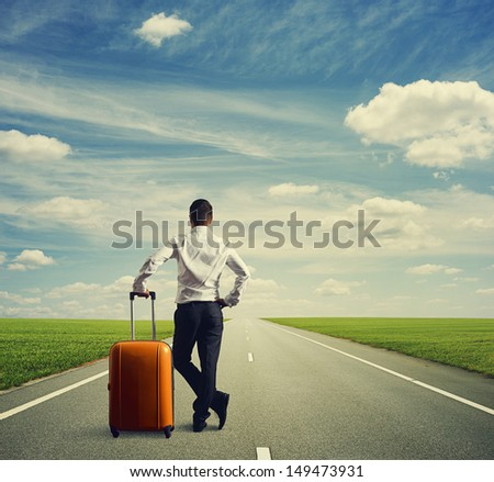 businessman with bag standing on road and looking forward - stock photo