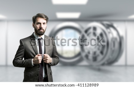 Businessman with bank vault in the background - stock photo