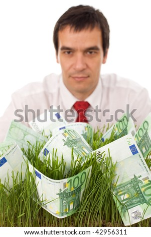 Businessman with banknotes in grass - green business concept, isolated, focus on foreground - stock photo