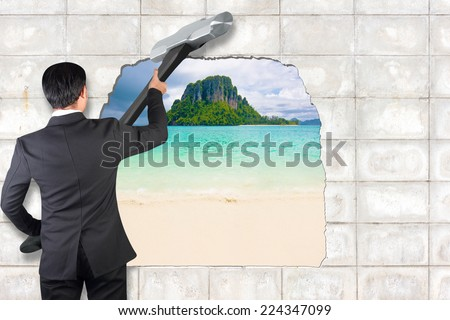 businessman with big hammer in hands against tropical island and beautiful sea Concept image about freedom of mind and unconventional thinking outside the box - stock photo