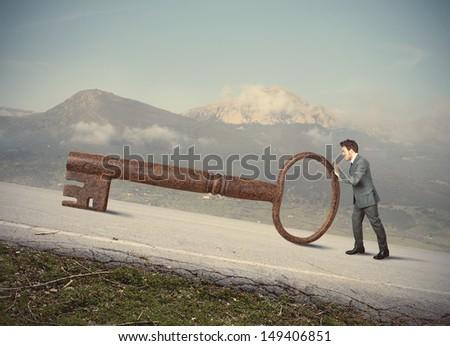 Businessman with big key to success - stock photo